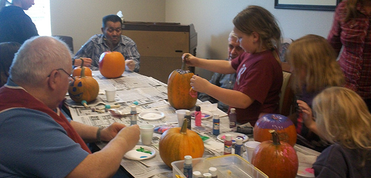 Residents and visitors hanging out and carving pumpkins together