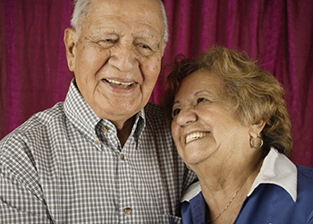 Elderly woman leaning against her husband's shoulder, looking up and smiling