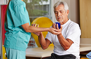 Resident working with small hand weights and a physical therapist