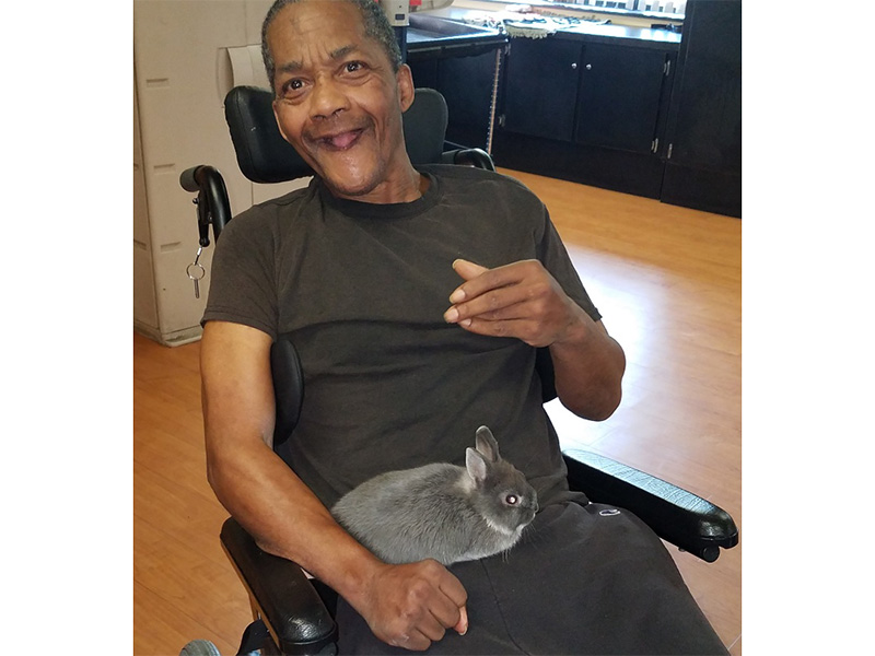 Resident smiling with a bunny in a wheelchair