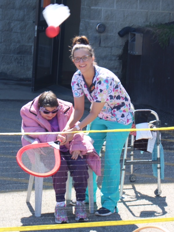 Staff helping residents play badmitton