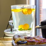 Fresh lemon and cucumber water with donuts and coffee
