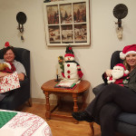 Two women sitting in chairs holding stuffed animals during the holidays