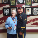 Nona and a soldier standing by the veteran wall