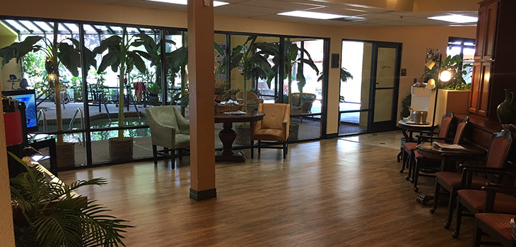 Lobby area with several spots for sitting and glass windows that show the indoor pool and spa