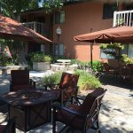 Patio area for residents with plenty of seating, a fire pit and large umbrellas for shade