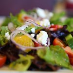 Salad with feta cheese and purple onions, mandarin oranges, tomatoes and lettuce