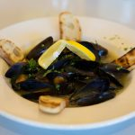 fresh muscle soup with toasted bread along the corners and a slice of lemon draped across the muscles