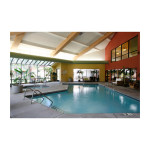 Indoor swimming pool and spa with plants alongside it and seating
