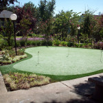 Golf putting green surrounded by walking paths with a beautiful garden