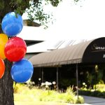 The entrance to the community with balloons tied to the trees
