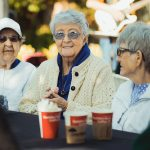 Three residents enjoying some hot coco outdoors with live music