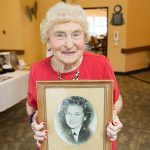 Resident holding up a picture of herself from her youth