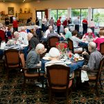 Residents in the dining room happily eating together