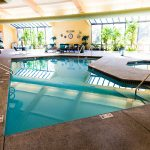 Beautiful indoor swimming pool and spa surrounded by plants and comfortable seating