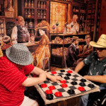 Residents playing checkers in front of a large wall mural