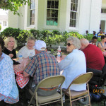 Colonial Haven residents gathered for an event eating at tables in front of the building