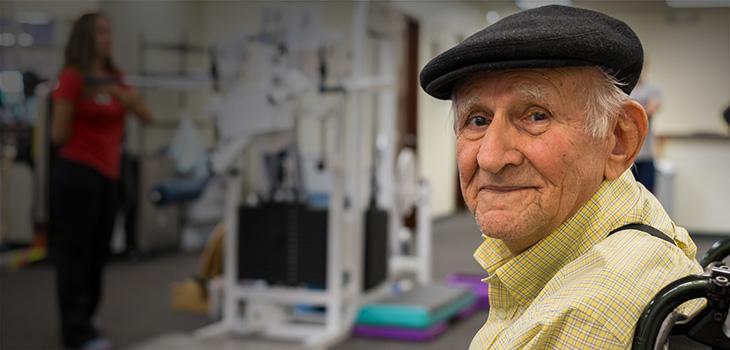 A man sitting in a wheelchair in a rehab gym
