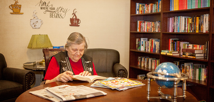 A resident sitting at a table reading a book from the library