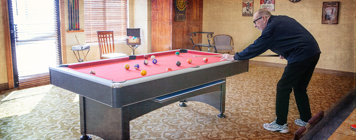 A resident playing a game of pool