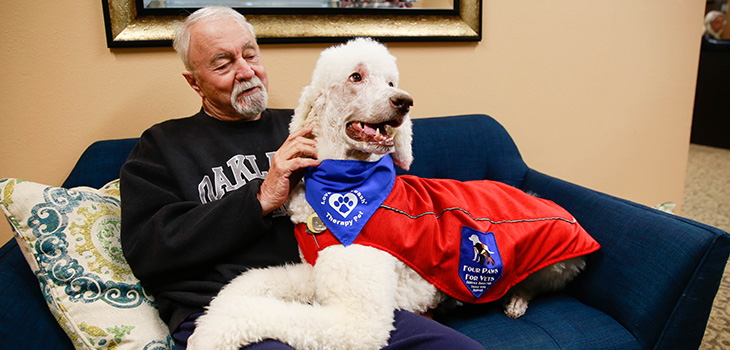 Resident enjoying his time with a therapy dog on a couch