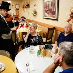 Residents being serenaded by a violinist at the dining table