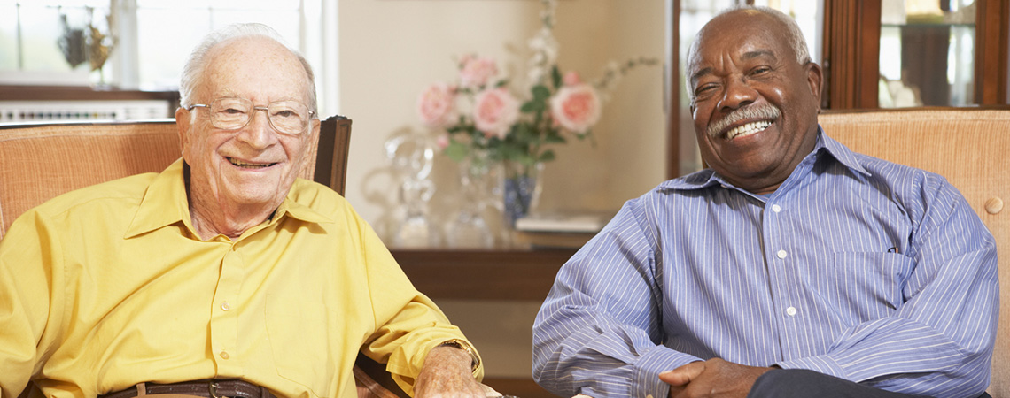 Two men sitting beside each other with large smiles on their faces.