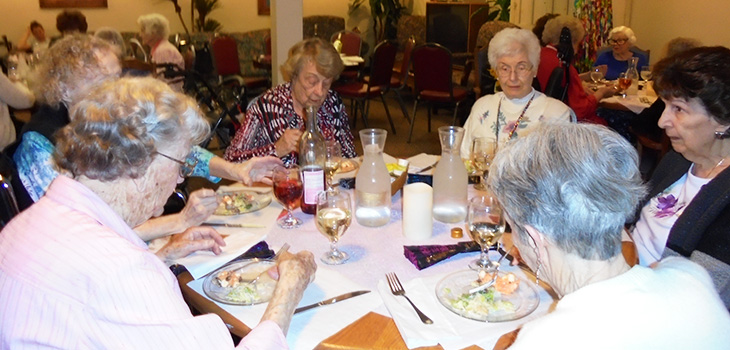 full table of residents enjoying food and drinks together