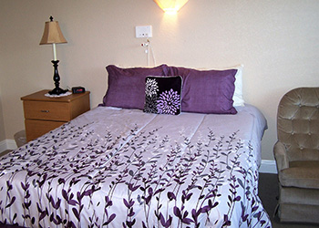 pretty lavender bedspread and decorative pillows in a resident's room