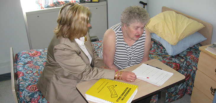 Staff member working with a patient on paperwork