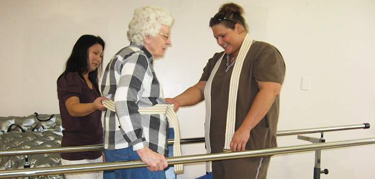 Rehabilitatoin staff assisting a resident with walking