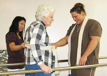 Rehabilitation staff assisting a resident with walking