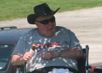 Resident with a cowboy hat on sitting outside in his wheelchair enjoying a treat