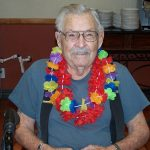 male resident smiling and wearing 2 Hawaiian leis for the party
