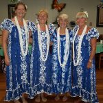 professional hula dancers wearing matching dresses and necklaces