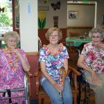 3 female residents dressed for the luau in festive outfits and wearing leis