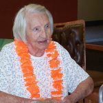 female resident wearing an orange lei for a luau party