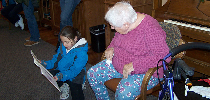 young visitor reading to a resident