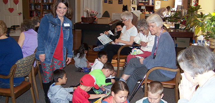 residents coloring with children visiting Sterling Heights