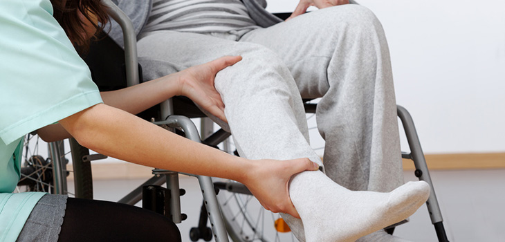 nurse helping resident stretch his legs