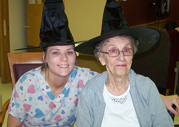 nurse and resident smiling together with halloween hats
