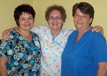 three nurses smiling together