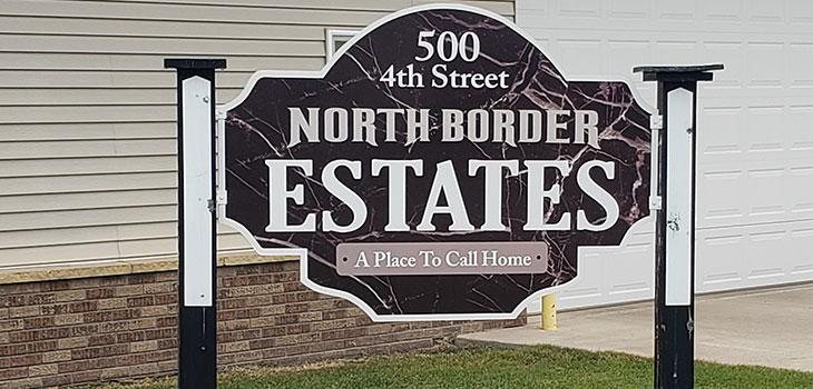 North Border Estates sign and green lawn