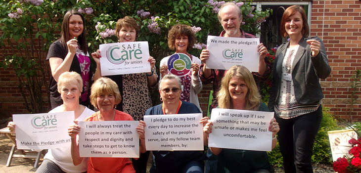 staff holding safe care signs