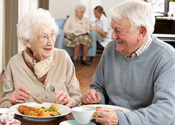 Elderly couple smiling fondly at each other while enjoying a meal together
