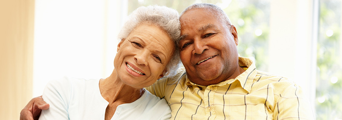 Elderly couple seated indoors smiling with their heads tilted together
