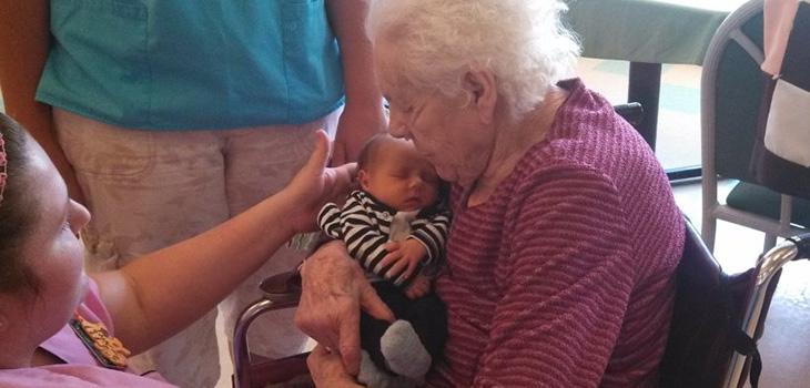 Resident holding a newborn sleeping baby