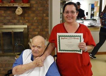 A resident receiving an award from a staff member