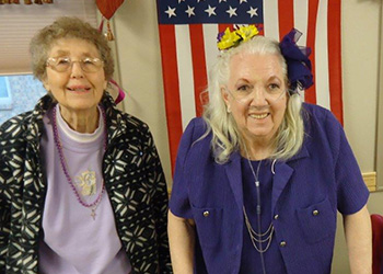 Two resident smiling together with an American flag in the background