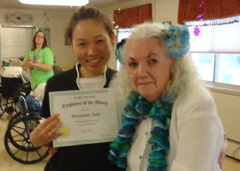 A resident and staff member with a certificate